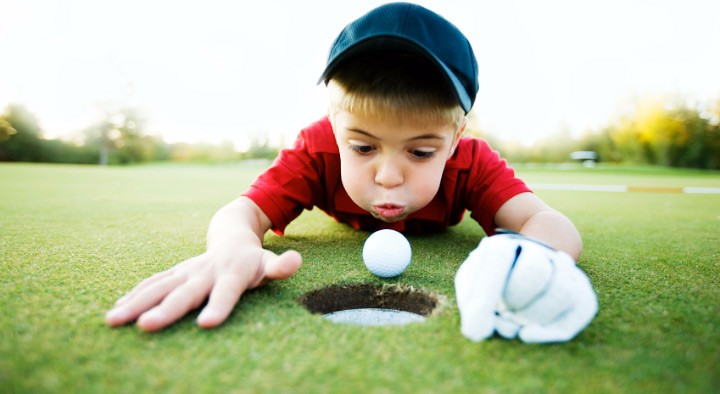 Kid-blowing-on-golfball